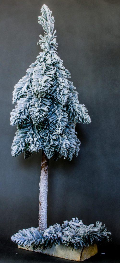 Biała choinka ze stroikiem na pniu pięknie ośnieżona
